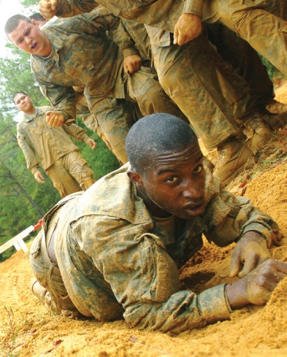 Cute black solider crawling in the sand during military boot camp