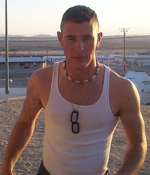 Young masculine army soldier in tanktop and uniform pants